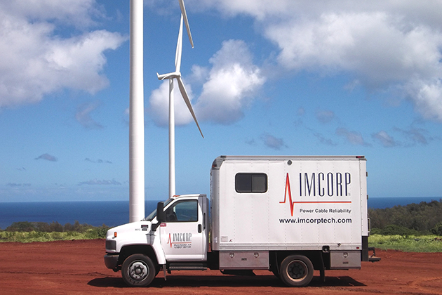 An IMCORP van in front of wind turbines in Hawaii. (Photo supplied by IMCORP)