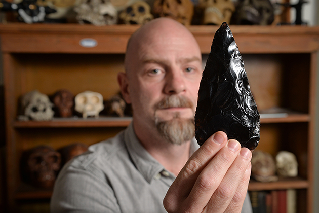 Daniel Adler, associate professor of anthropology, with a stone tool at his office in Beach Hall. (Peter Morenus/UConn Photo)