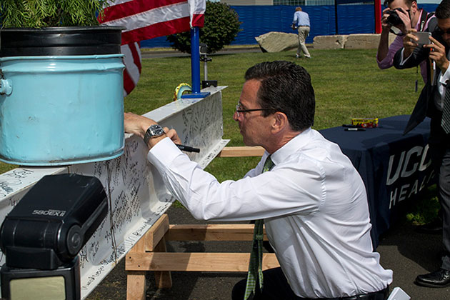 Gov. Dannel P. Malloy signs a steel beam that will become part of the structure, during a topping-out ceremony for the new hospital tower on Sept. 8, 2014. (Tina Encarnacion/UConn Health Photo)