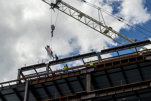 The final steel beam, signed by Gov. Dannel P. Malloy and others, is hoisted into place on the UConn Health hospital tower, part of the Bioscience Connecticut initiative at the Farmington campus. (Tina Encarnacion/UConn Health Photo)
