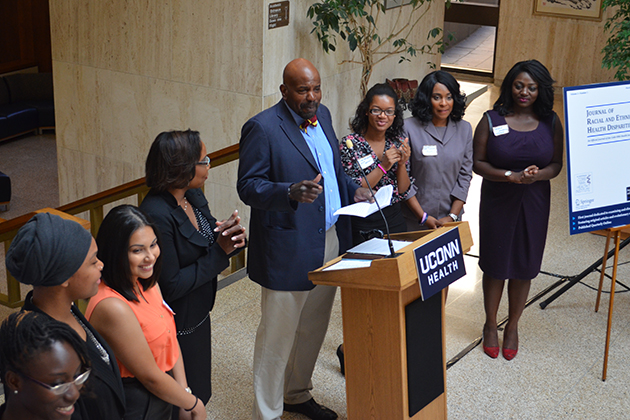 Dr. Cato Laurencin addresses participants in the CICATS Young Innovative Investigator Program during the CICATS Health Disparities Science Cafe on Sept. 17, 2014, in the Academic Lobby at UConn Health. From left, Melissa Carr-Reynolds, Akilah Plair, Sandra Lopez, Dr. Linda Barry, Nilse Dos Santos, La Shondra Ellis, and Trisha Kwarko. (UConn Health Photo)