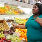An overweight woman selecting fruits in a grocery store. (Rudd Center on Obesity Research and Policy Photo)