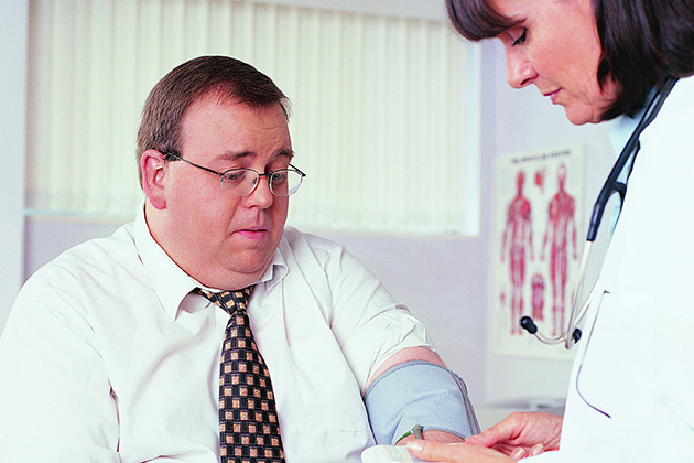 An overweight businessman has his blood pressure taken by a doctor. (Thinkstock/UConn Photo)