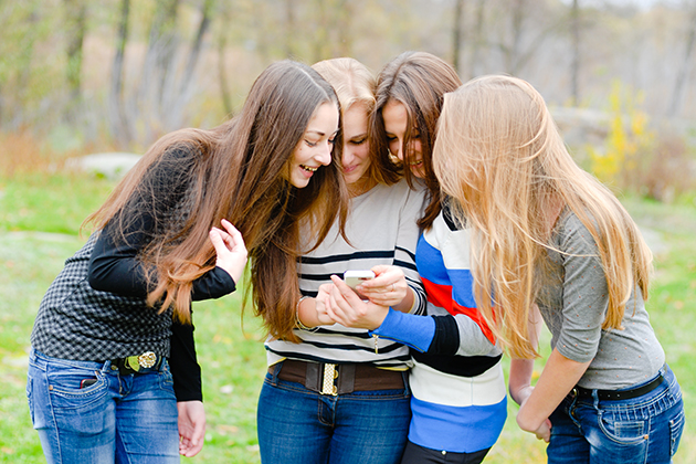 A group of teenagers crowd around to look at a smartphone one of them is holding. (Shutterstock/UConn Health Photo)