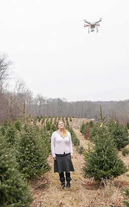 Jill WEgrzyn looks up at a drone flying overhead at a Christmas tree farm. Researchers now use drone technology to survey forests and orchards. (Sean Flynn/UConn Photo)