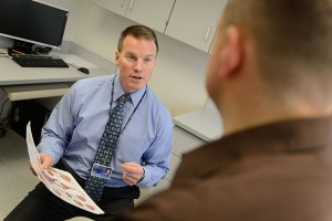Dr. John Taylor meets with a urology patient at Dowling South at UConn Health in Farmington. (Peter Morenus/UConn Photo)