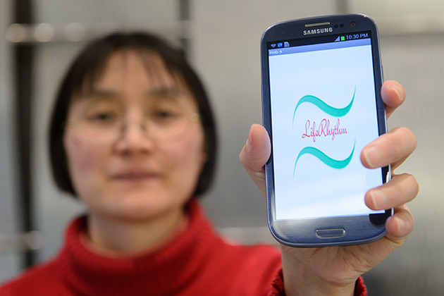 Bing Wang, associate professor of computer science and engineering, holds a smartphone with an application created to help monitor people with depression. (Peter Morenus/UConn Photo)