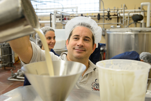Bill Sciturro, manager of dairy manufacturing in the animal science department, pours a test batch of reduced-sugar ice cream into a batch freezer. (Peter Morenus/UConn Photo)