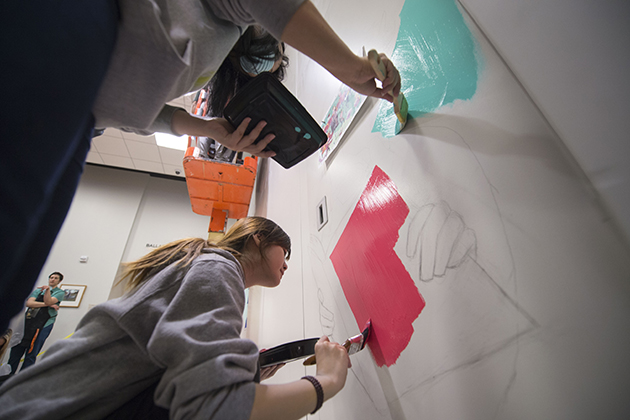 Fine arts students paint a mural at the UConn Co-op Bookstore. (Peter Morenus/UConn Photo)
