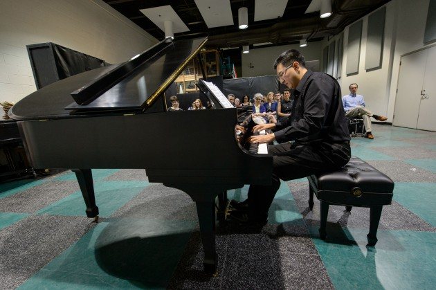 Graduate student Mo Tien plays for an assembled group of students, faculty and staff on a new Steinway & Sons grand piano just delivered to the Music Building on May 7, 2015. (Peter Morenus/UConn Photo)