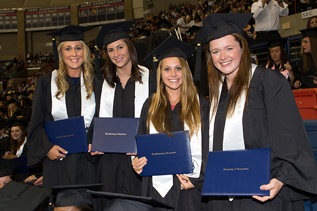 From left, Devon Mangle and Karson Ratliff (Volleyball), Chrissy Davidson and Chloe Hunnable (Field Hockey), all Class of 2015, holding their degree certificatesat Commencement in Gampel Pavilion. (Stephen Slade '89 (SFA) for UConn)