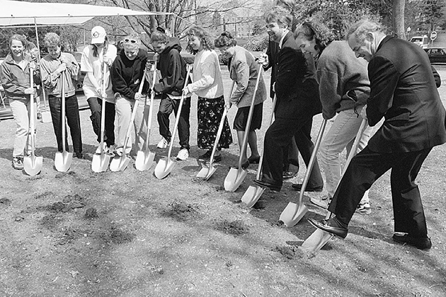 """University officials and students joined to break ground Wednesday on the new South Campus residence hall and dining facility complex, set to open in September 1998.  Five lucky students-Suzanne Zajkowski, Alison Burdick, Sarah Aller, Kerry Landers and Kara Medalis-won a raffle guaranteeing them a room in the dorms, which will be one of the most modern residence halls in the nation.  About 200 people gathered to share in the moment, including Lewis Rome, chair of the Board of Trustees (far right), a former resident of the old South Campus dorms.  Presdient Philip E. Austin said it was a day of great hope and aspiration for an even better UConn.  """"It may look like a war zone, but it's a metaphor for progress,"""" Austin said.  PHOTO BY PETER MORENUS"""