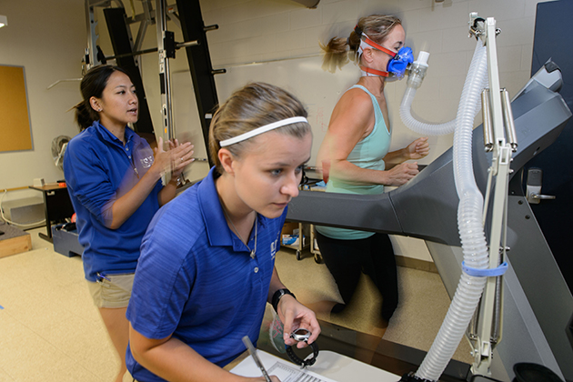 A woman soon to run in the Falmouth Road Race, right, is tested at the Korey Stringer Institute by Rachel Katch, center, and Yuri Hosokawa. (Peter Morenus/UConn Photo)
