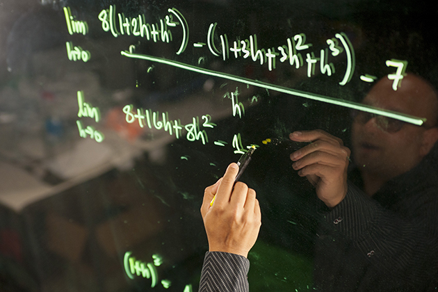 Amit Savkar, assistant professor-in-residence of mathematics, records a lecture using lightboard technology on Sept. 18, 2015. (Sean Flynn/UConn Photo)