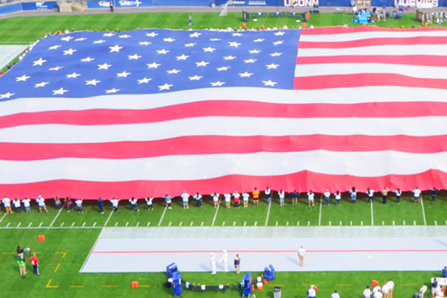 Volunteers unfurl a giant flag before the start of the UConn vs Navy football game on Sept. 26, 2015. (Ryan Glista '16 (CLAS)/UConn Photo)