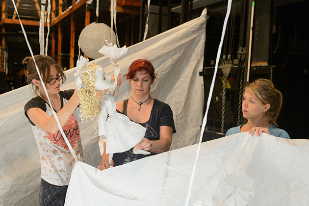 Sarah Nolen '15 MFA, left, Ceili Clemens '01 (SFA), and Lucia Rich, a professional performer, operate the puppet 'Aya' during a rehearsal for 'Unfolding the Story: A Journey of Her Own' at the Studio Theater on Sept. 11, 2015. (Peter Morenus/UConn Photo)