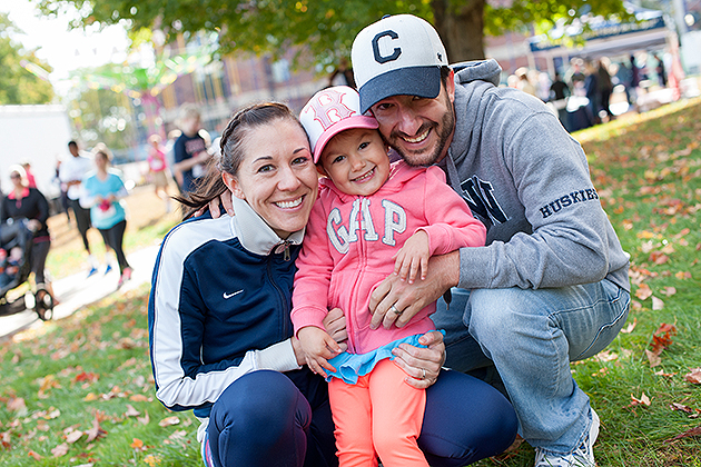 Alumni Christine '03 (SFA) and Kevin Ballestrini '04 (CLAS) pose with their daughter Livia. (Roger Castonguay for UConn)