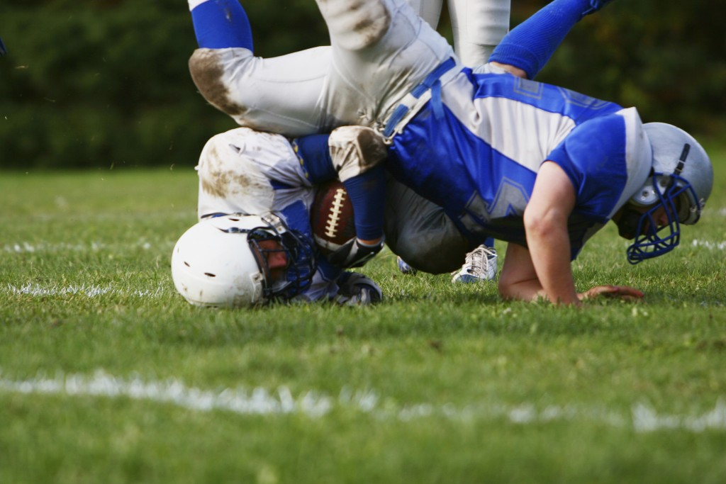 A football player falls during a game. (iStock Photo)