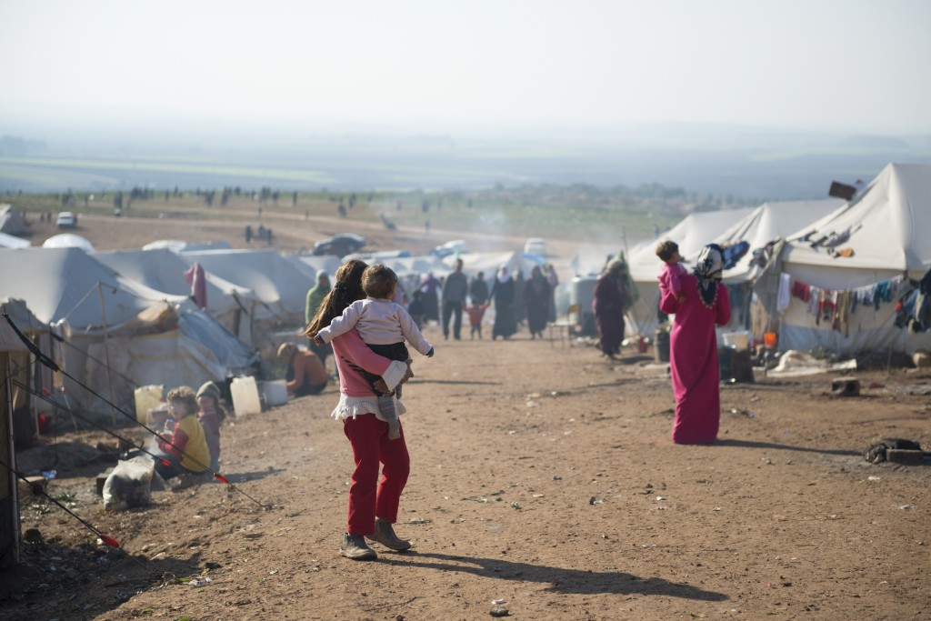 Syrian refugees walk outside their tents at a camp for internally displaced persons in Atmeh, Syria, adjacent to the Turkish border. (iStock Photo)
