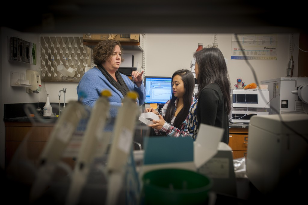 From left, pharmacy professor Marcy Balunas speaks with Anne Sung '17 and graduate student Samantha Gromek on Dec. 17, 2015. (Sean Flynn/UConn Photo)