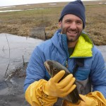 Mark Urban, researcher of ecology and evolutionary biology, holds an Arctic grayling in Alaska.