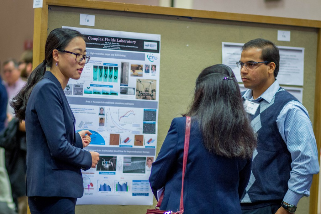 Two graduate students in engineering, Yang Guo, left, and Huseini Patanwala, speak with an industry partner during the School of Engineering's Open House in November 2015. (Chris LaRosa/UConn Photo)