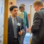 Arash Zaghi, assistant professor of civil and environmental engineering, left, speaks with industry partners during the School of Engineering's Open House in November 2015. (Chris LaRosa/UConn Photo)