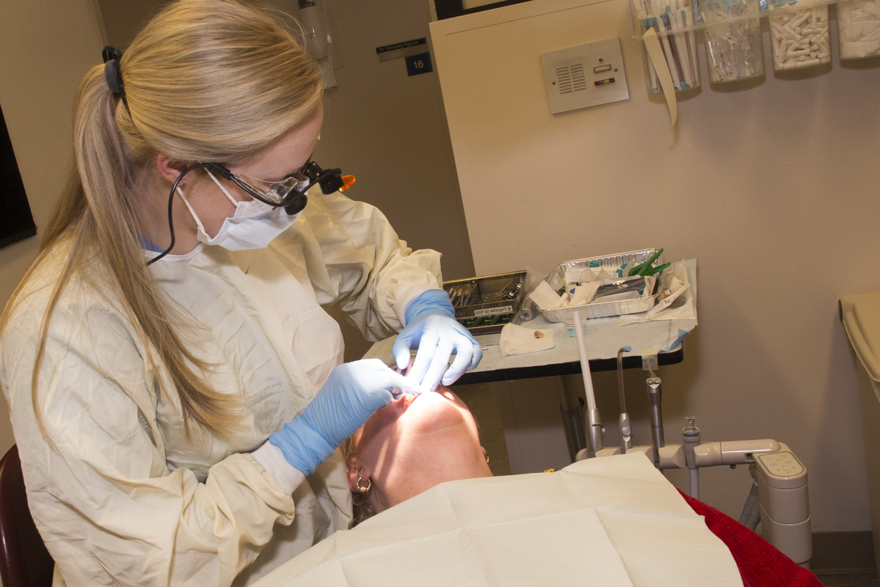 Dental resident Roberta Wright tends to a patient. (Janine Gelineau/UConn Health Photo)