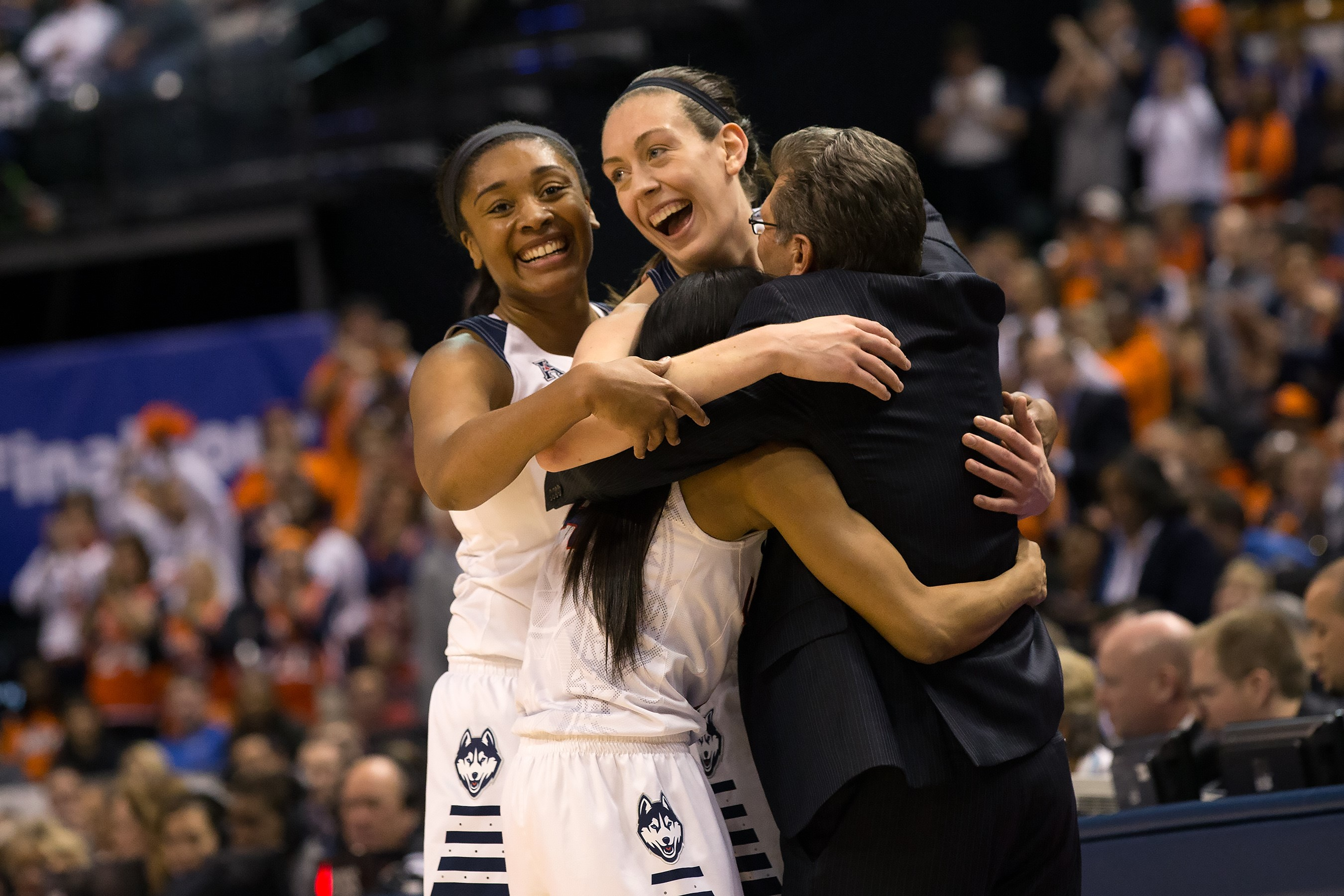 Seniors Morgan Tuck, Breanna Stewart, and Moriah Jefferson celebrate their fourth national title in a row with head coach Geno Auriemma. (Stephen Slade '89 (SFA) for UConn)