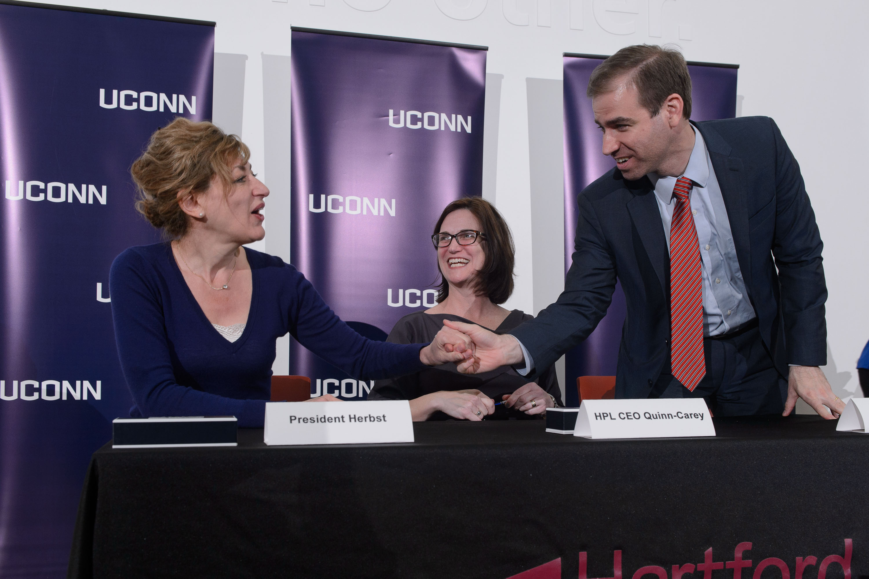 President Susan Herbst, left, HPL CEO Bridget Quinn-Carey and Mayor Luke Bronin shake hands on April 21, 2016 after signing an agreement to host the new downtown UConn Hartford library at the Hartford Public Library. (Peter Morenus/UConn Photo)