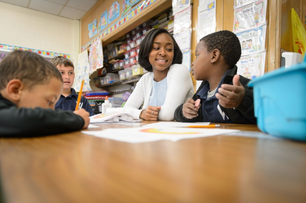 Symone James '16 (ED), a student teacher at W.B. Sweeney School in WIllimantic, helps students with reading. (Peter Morenus/UConn File Photo)