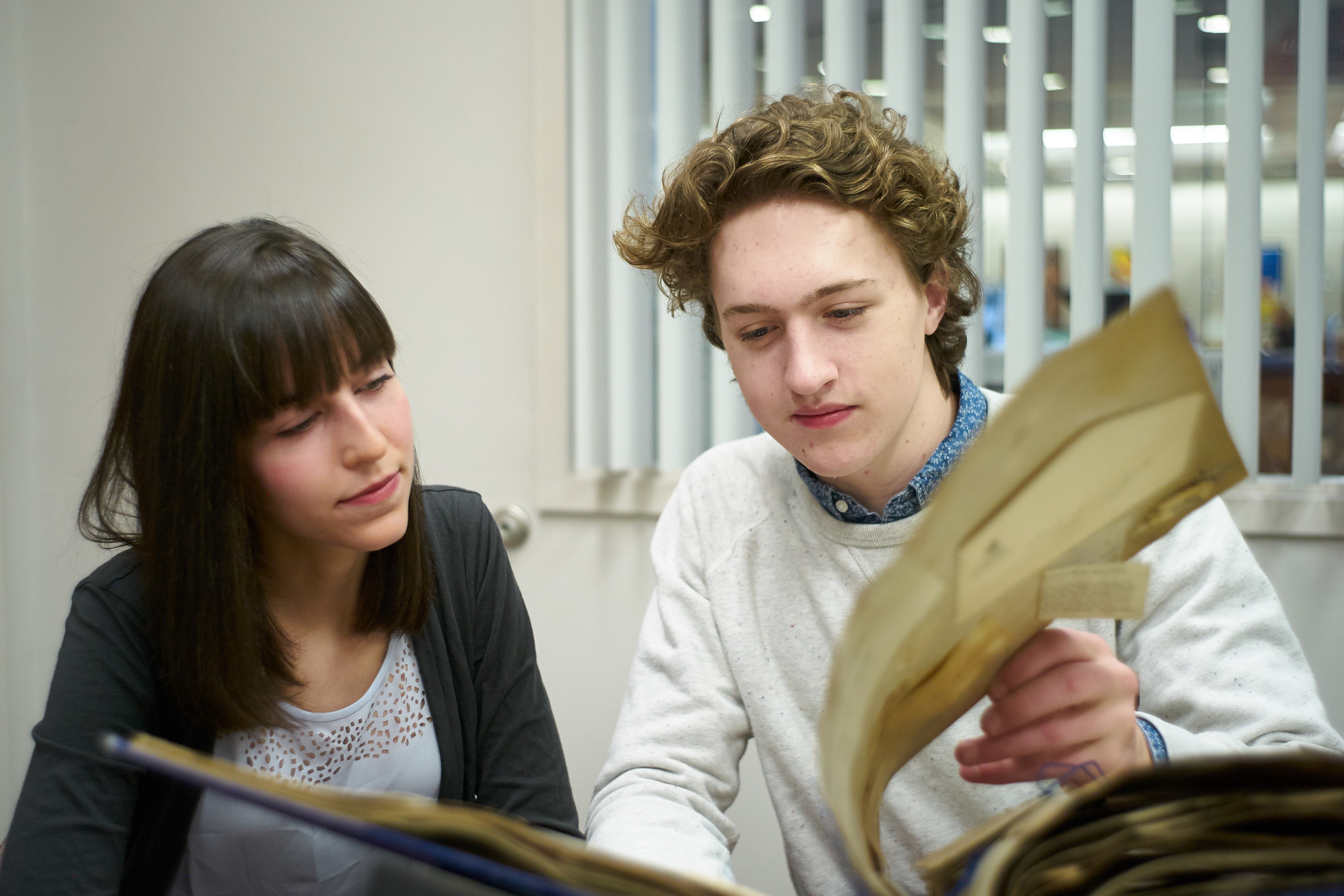 Helen Stec '18 (CLAS) and Charles Smart '18 (CLAS) review a scrapbook from the early 1920s kept by Flora Howe '25 at the University Archives on April 6, 2016. (Peter Morenus/UConn Photo)