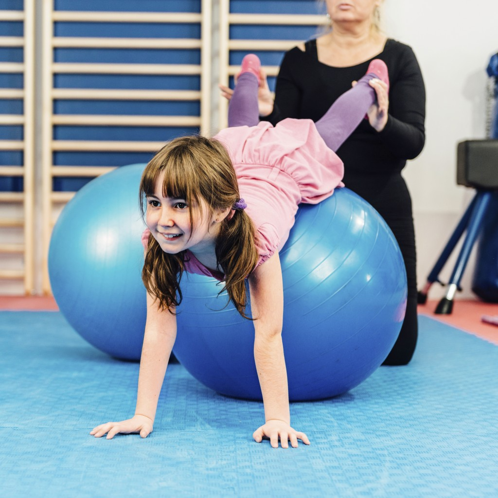 Girl exercising on pilates ball with instructor's help. (iStock Photo)