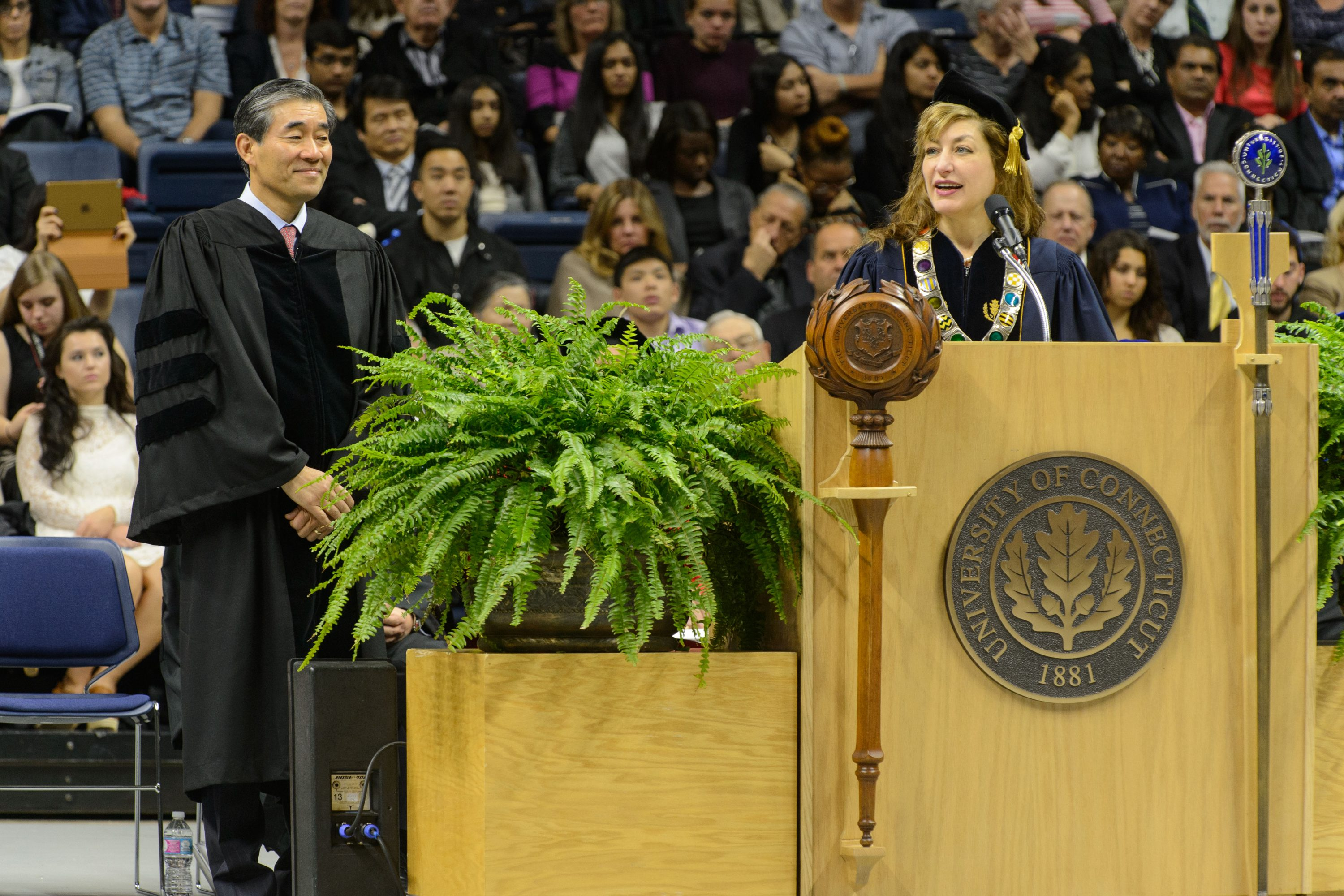 President Susan Herbst reads the citation to award John Kim '87 MBA an honorary degree during the School of Business commencement ceremony at Gampel Pavilion on May 8, 2016. (Peter Morenus/UConn Photo)