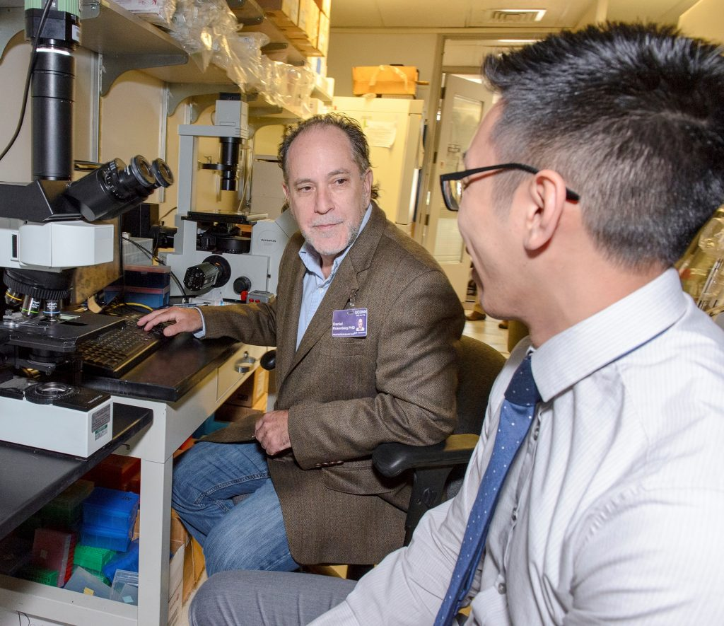 Dan Rosenberg, left, and Allen Mo use a technique called laser capture microdissection to select small groups of cells from a biopsy, which enables them to screen for mutations. (Janine Gelineau/UConn Health Photo)