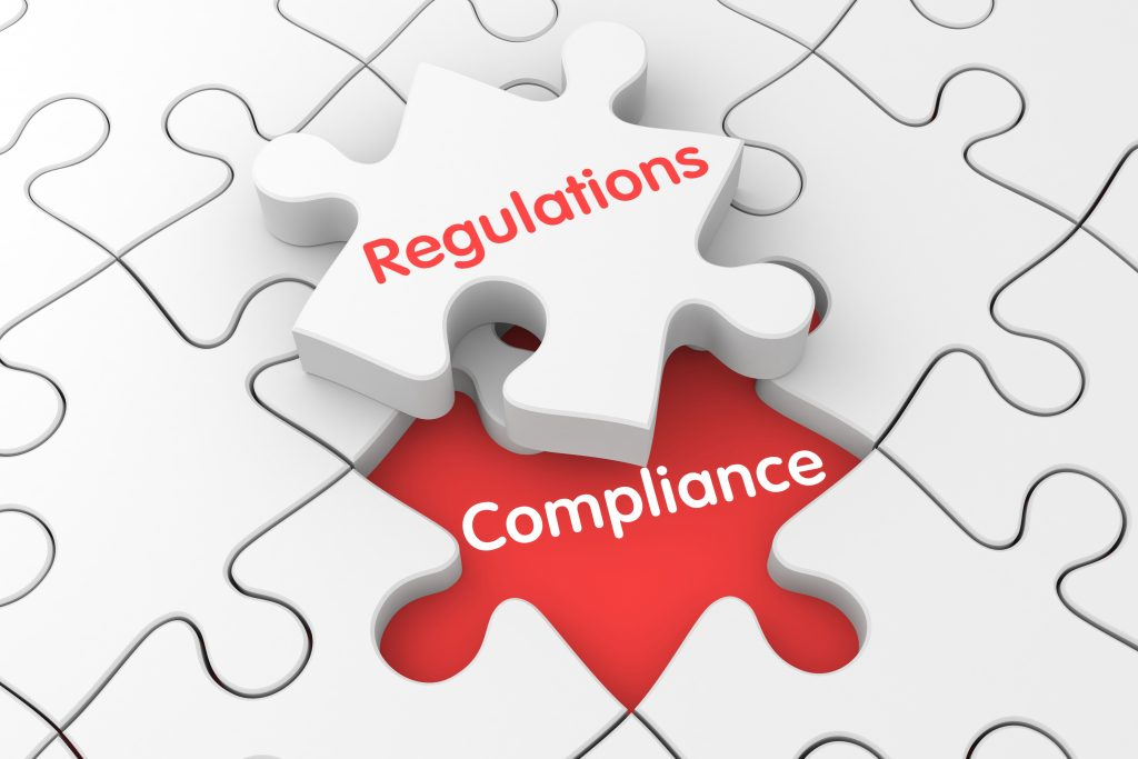 A jigsaw puzzle, with one piece ('regulations') that is detached from the others, and the remaining space is labeled 'compliance.' (iStock Photo)
