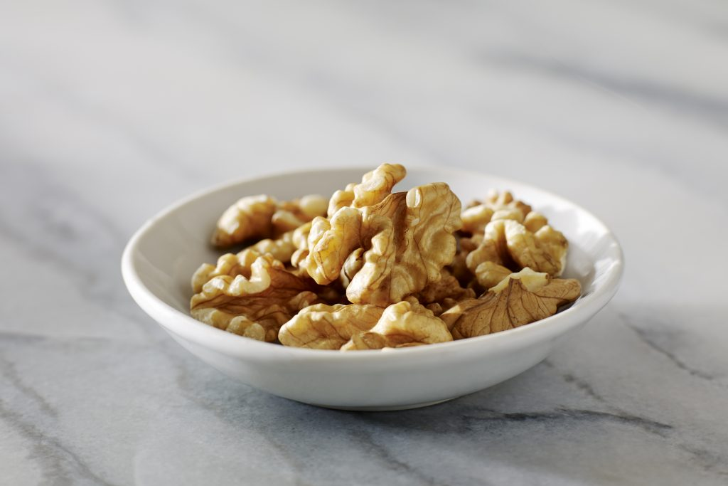 Walnuts in a dish on a marble background. (Photo: California Walnut Commission)