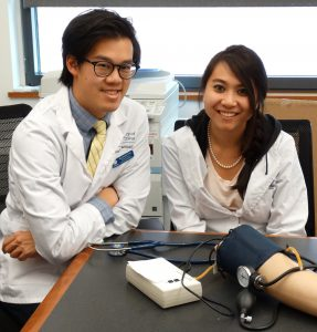 Pharmacy students with blood pressure simulation arm.