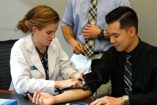 Pharmacy students learning to take blood pressure readings.