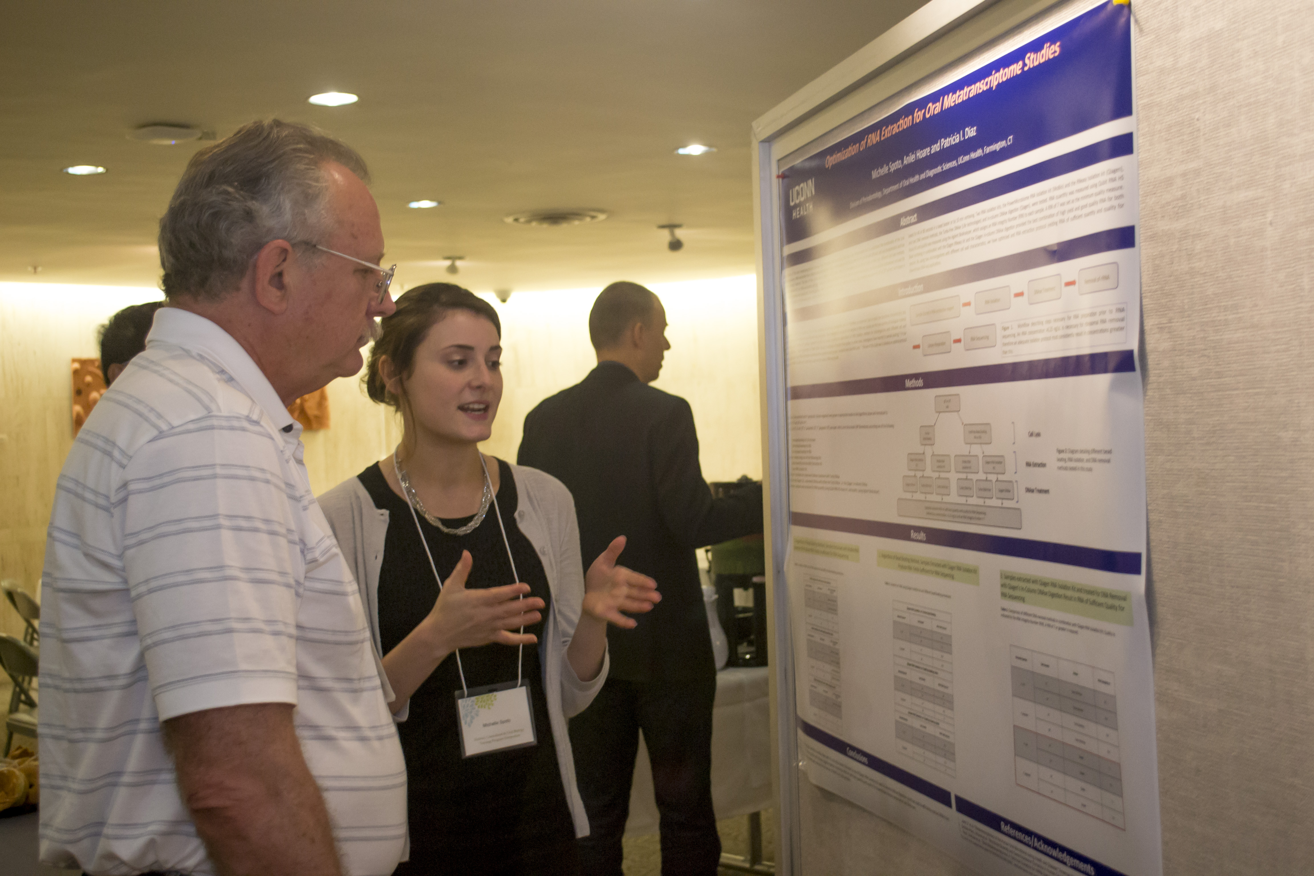 PhD student Michelle Spoto explaining her research poster to reconstructive sciences researcher Alex Lichtler during the Skeletal, Craniofacial and Oral Biology annual symposium Monday at UConn Health. (Photo by Tina Encarnacion)