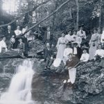 The Connecticut Agricultural College Summer School Picnic, 1907: Twenty-five women and four men sitting on rocks around a small waterfall in the woods off Codfish Falls Road in Mansfield. (University Photograph Collection, Archives & Special Collections, UConn Libraries)