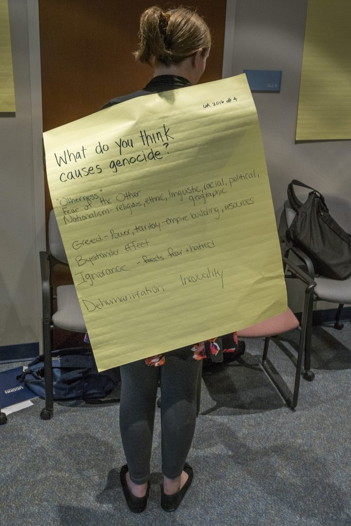 A participant in the 2016 Intellectual Humility in Secondary Education Summer Institute displays a worksheet with answers to the question, What do you think causes genocide? at the Thomas J. Dodd Research Center on Aug. 1, 2016. (Sean Flynn/UConn Photo)