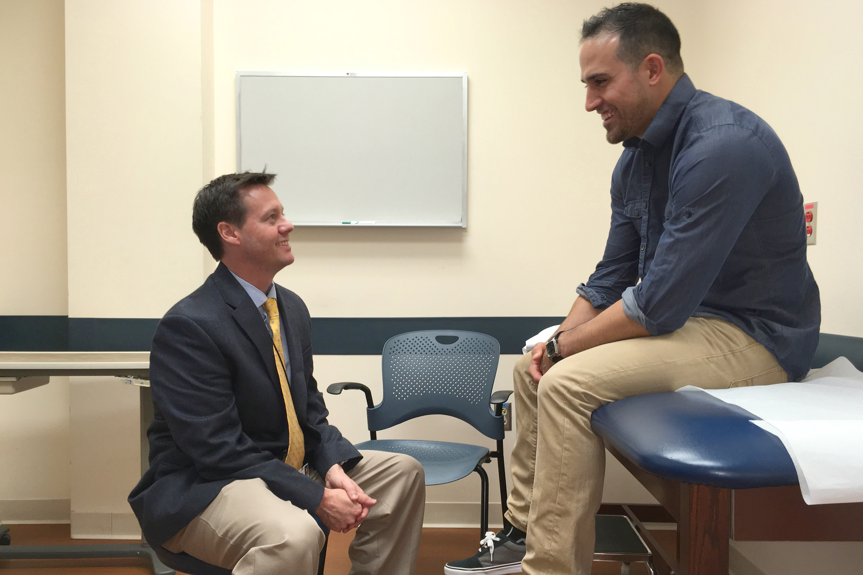 Sports medicine expert Dr. Cory Edgar speaks with Anthony Giansanti of Montville, Conn., at a follow-up appointment at UConn Health. (Lauren Woods/UConn Health Photo)