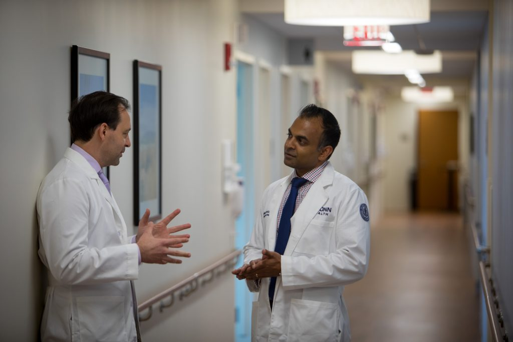 Dr. Alex Merkulov, left, head of women's imaging at UConn Health, speaks with Dr. Amish Patel, the first graduate of the breast imaging fellowship at the UConn School of Medicine, in the hallway of the Women's Center Imaging Suite at UConn Health. (Paul Horton for UConn)