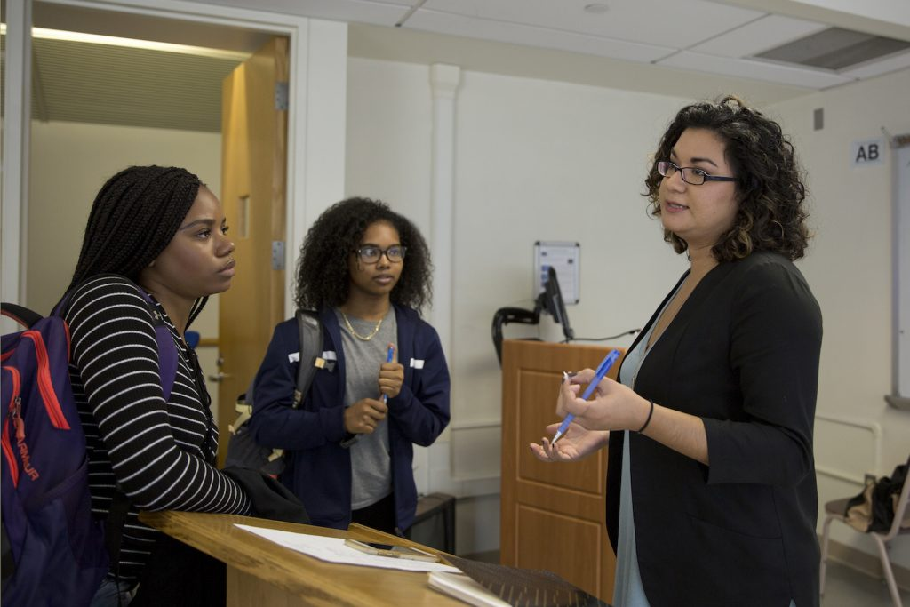 Postdoctoral fellow Shannon Gleason, who teaches the course 'Gender, Culture and Science,' speaks with Arabia Henley '18 (CLAS), left, an English major, and Moesha Outar '20 (CLAS), a math major, after midterm presentations. (Bri Diaz/UConn Photo)