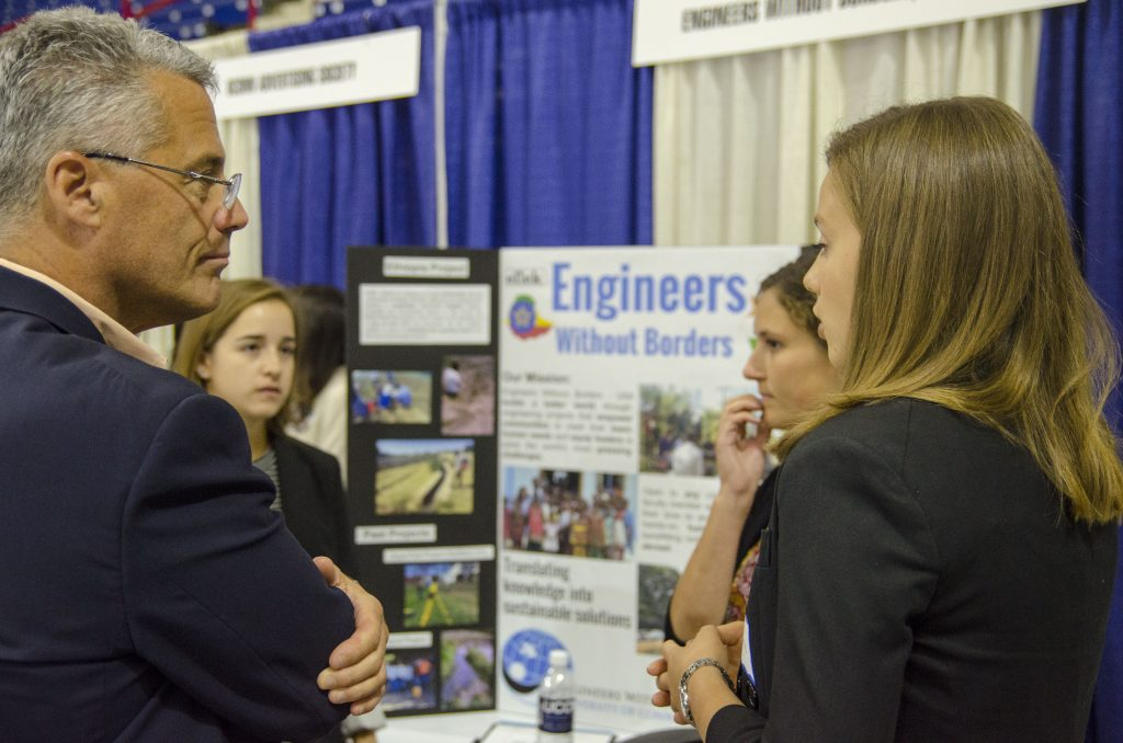 From left, Jennifer Skoog '19 (ENG), Megan Leether '17 (ENG), and Georgina Talbot '17 (ENG), speak with business leaders about Engineering without Borders at Gampel Pavilion. Oct. 5, 2016. (Garrett Spahn '18 (CLAS)/UConn Photo)