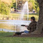 Playing the guitar at Mirror Lake on Sept. 26, 2016. (Sean Flynn/UConn Photo)