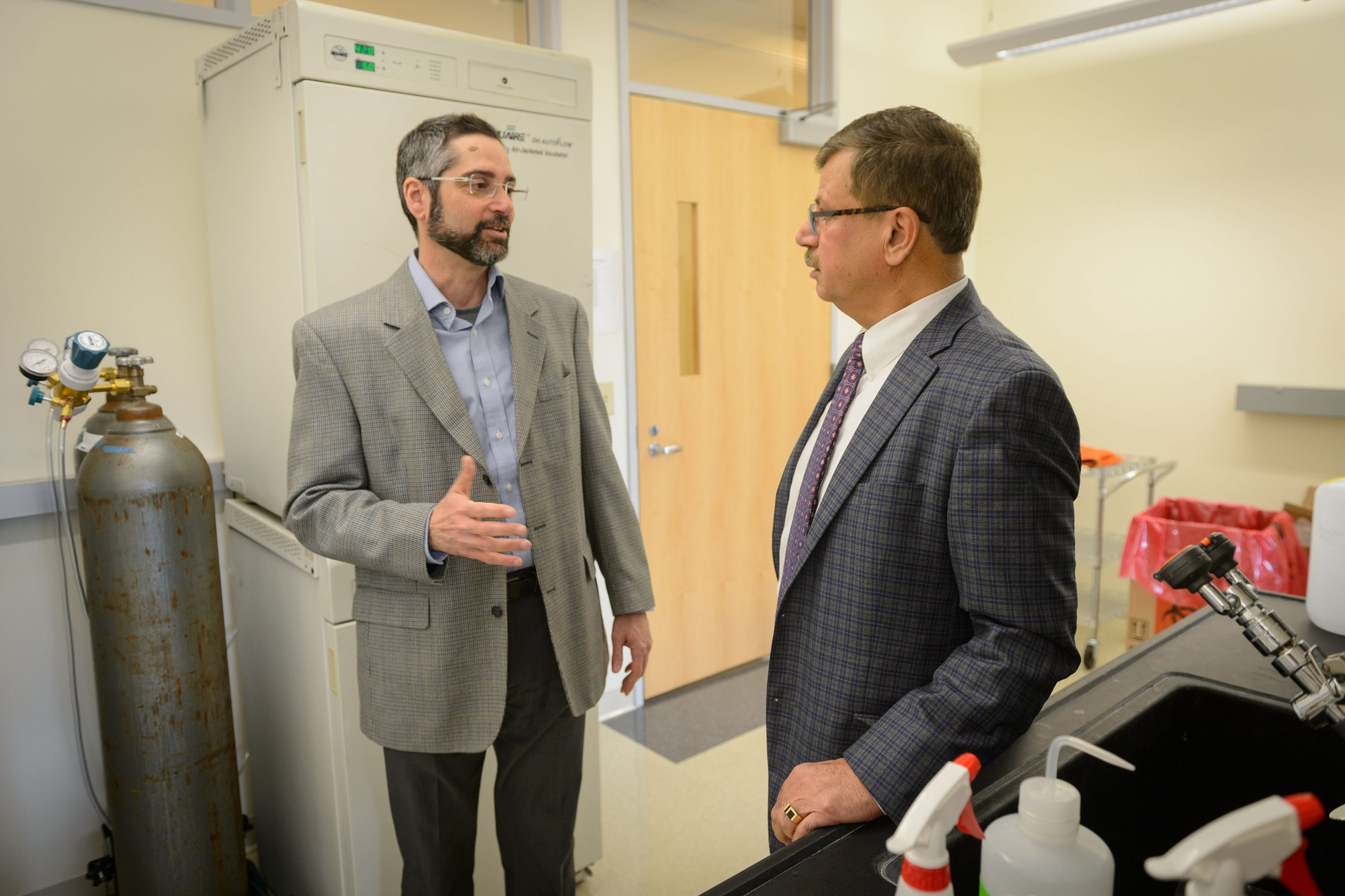 Anthony T. Vella, professor and Boehringer Ingelheim chair in immunology, left, speaks with President and CEO, Bijan Almassian at CaroGen Corp.'s technology incubation lab in Farmington on Dec. 12, 2016. (Peter Morenus/UConn Photo)