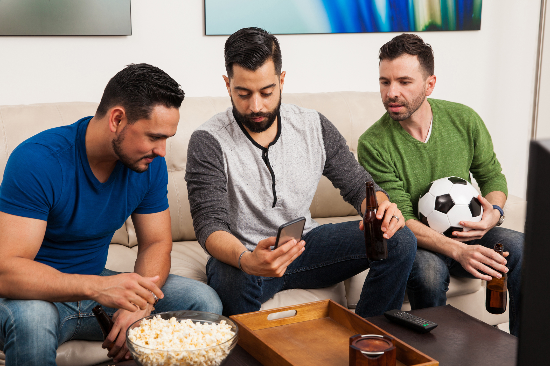 Group of friends checking their team stats on a smartphone while watching a soccer game on TV. (Antonio_Diaz/Getty Images)