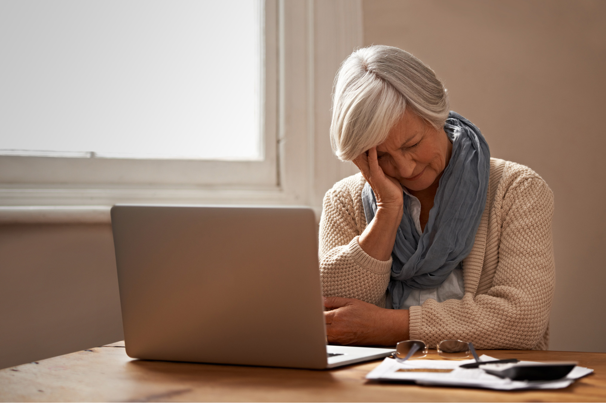 An elderly woman sitting in front of her laptop looking stressed. (PeopleImages via Getty Images)